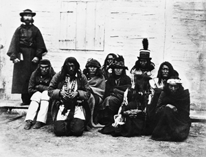 Picture of Jean L'Heureux in a cassock with a group of Blackfoot, Blood and Peigan Indians
